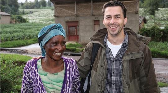 Michael Novoszad (CEO Likano) steht mit Ancille Mukasine vor einem Haus im Dorf