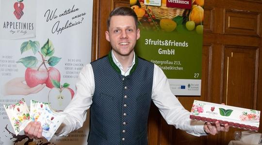 Lukas Wilfling in Tracht mit seinen Appletinies Produkten, an einem Ausstellerstand.