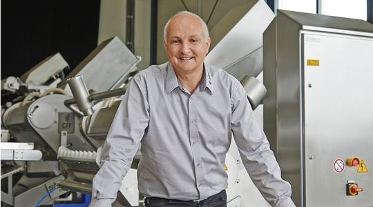 lächelnder Mann im Hemd  vor einer Maschine der Insort GmbH