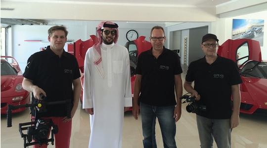 Andreas Breitschädel mit seinem Team bei Scheich Mohammed Khalid Abdul Rahim in einem Raum mit Sportwagen