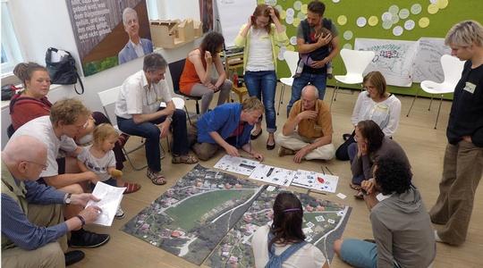 Baugruppenwerkstatt: Eine größere Gruppe bespricht Pläne