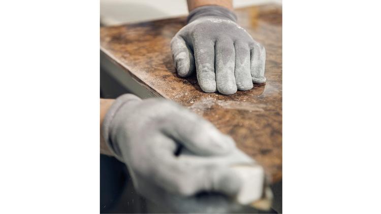 Hände mit Handschuhe, die gerade ein Werkstück schleifen