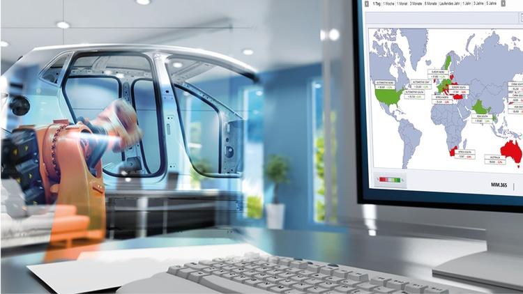 Computerbildschirm und Tastatur im Vordergrund. Maschine die an einer Autokarosserie arbeitet im Hintergrund.