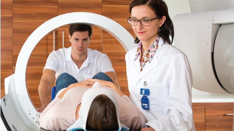 Person liegt in einem medizinischen Gerät und wird von Fachpersonal betreut