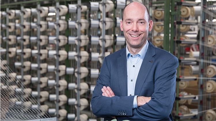 Geschäftsführer Martin Grübener hinter einer Textilmaschine