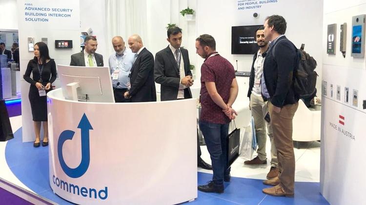 Eine Gruppe von Männern am Stand der Commend International GmbH bei der