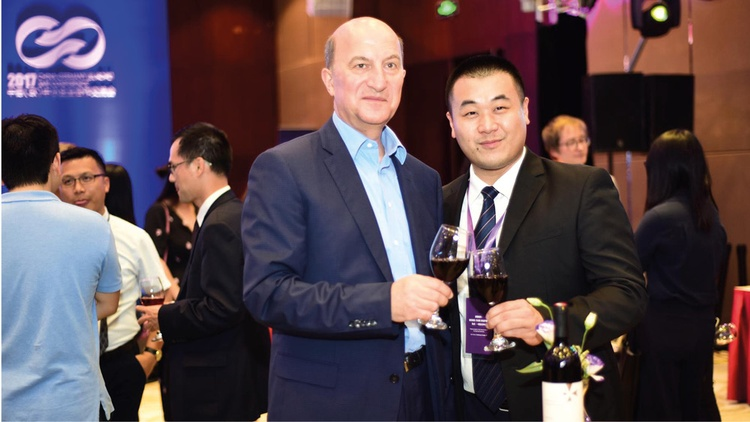 Michael Höferer und der chinesische Unternehmer Wu Kedong stoßen mit Deutschkreutzer Rotwein an.