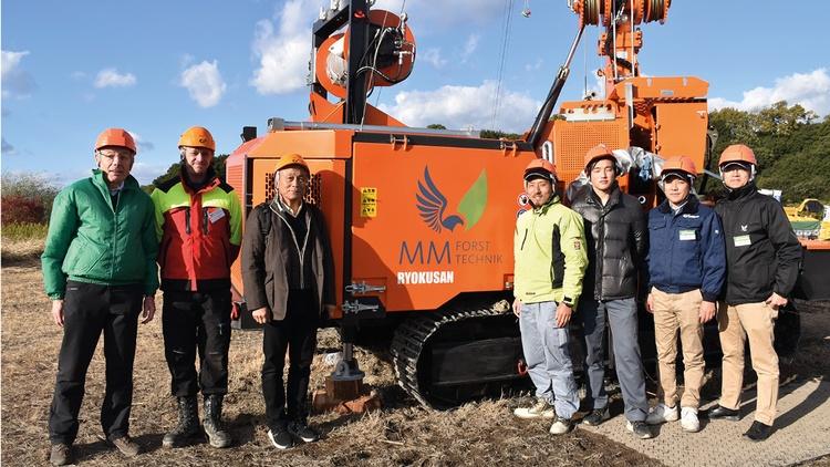 Mitarbeiter stehen bei einer Forstmaschine in Japan