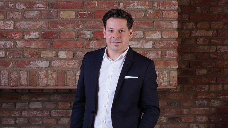 Portrait von Geschäftsführer Michael Schwarzenbacher vor einer Backsteinmauer