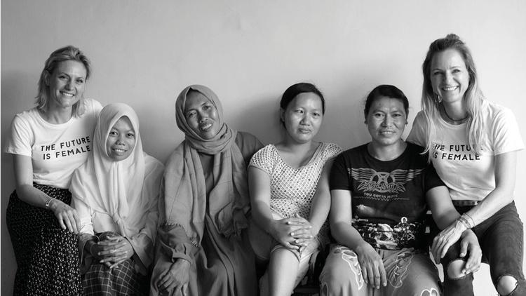 Sechs sitzende Frauen lächeln in die Kamera