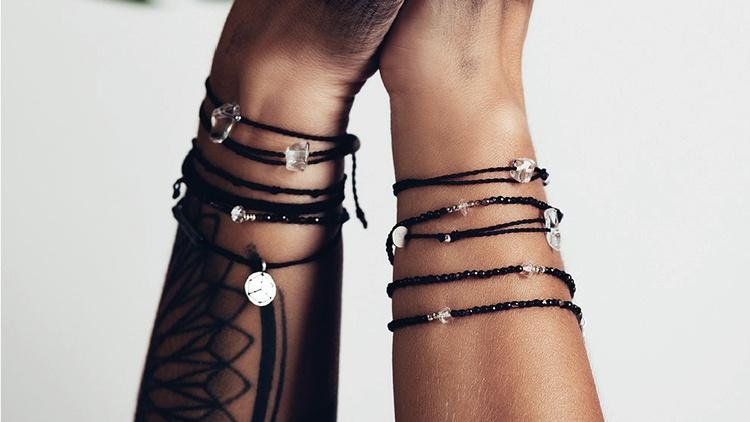 Zwei Arme deren Hände einander festhalten. Beide tragen Wunsch Kristall Armbänder. Der linke Arm hat ein Tattoo.