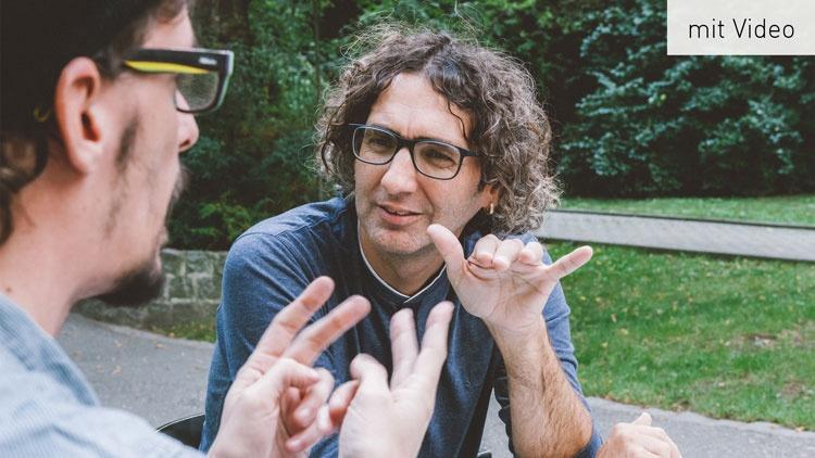 Zwei Männer unterhalten sich in Gebärdensprache