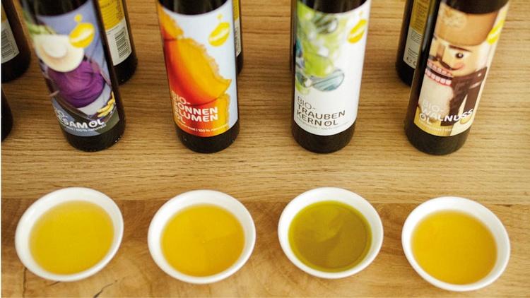 Ölfläschchen und Tassen mit Öl zum Verkosten