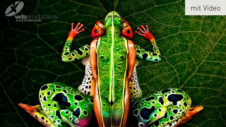 mit Bodypainting bemalte Menschen formen das Bild eines Frosches