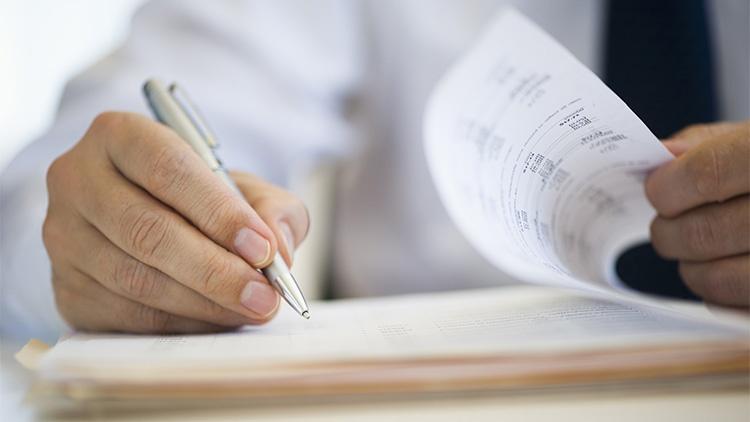 Eine Hand einer Person mit Hemd und Krawatte blättert Dokumente durch und die andere hält einen Kugelschreiber