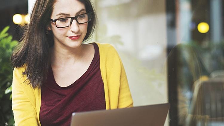 Eine junge Frau mit Brille blickt auf ihren Notebook-Bildschirm