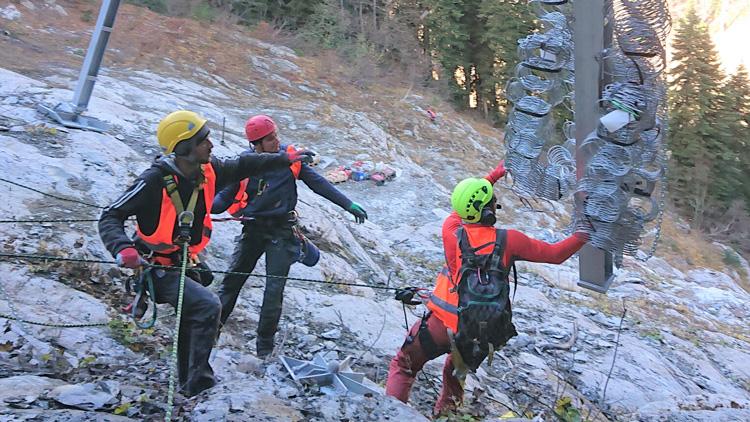 Drei Personen mit Schutzkleidung in gebirgigem Gelände